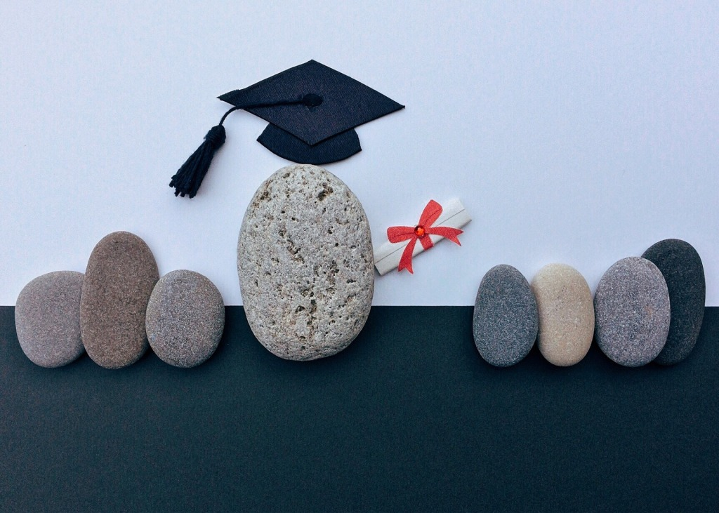 A pebble dressed up as a graduate with a scroll.
