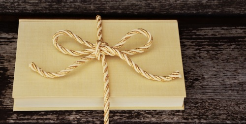 Image of a yellow book tied up with a string bow